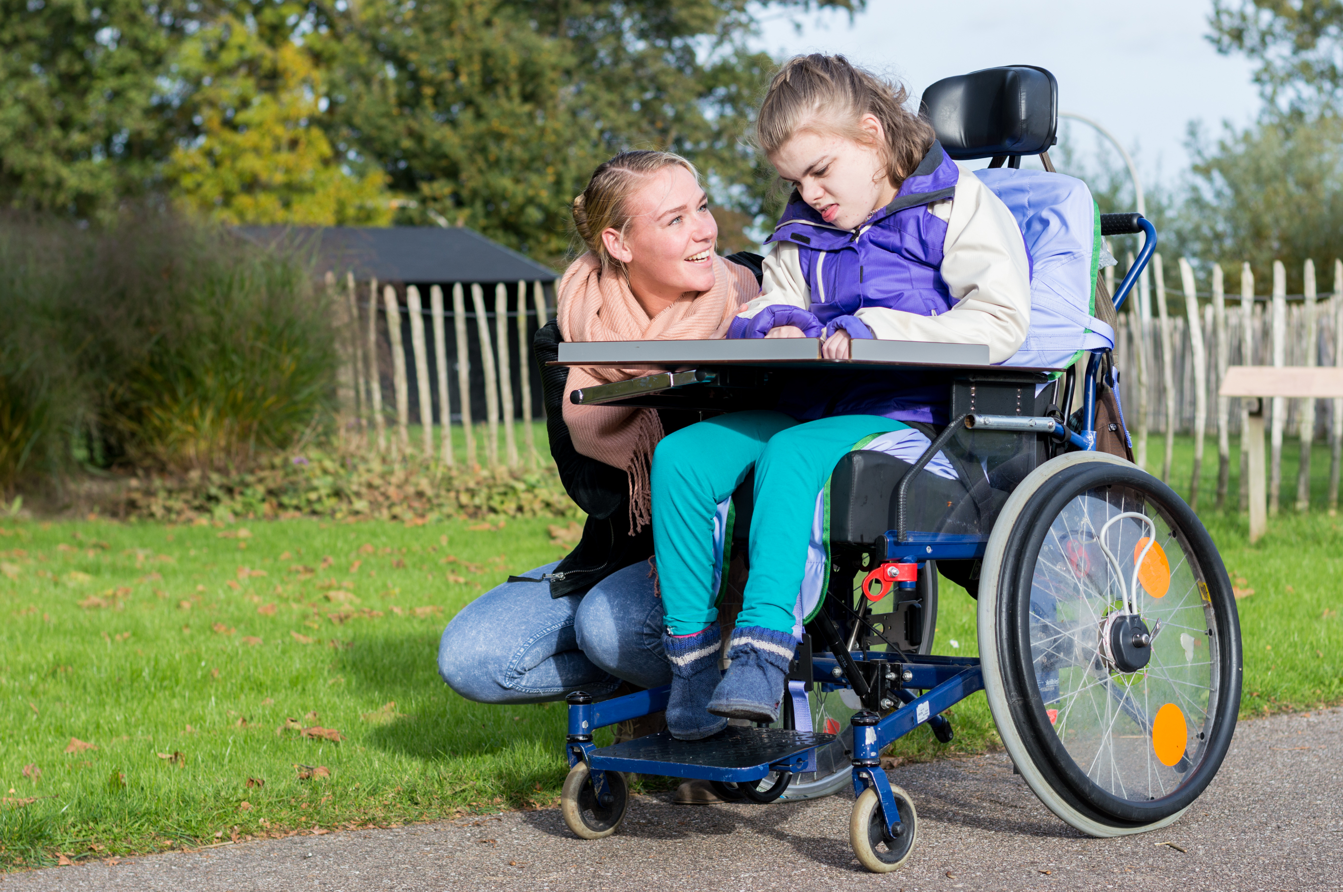 Disability a disabled child in a wheelchair relaxing outside together with help from a care assistant